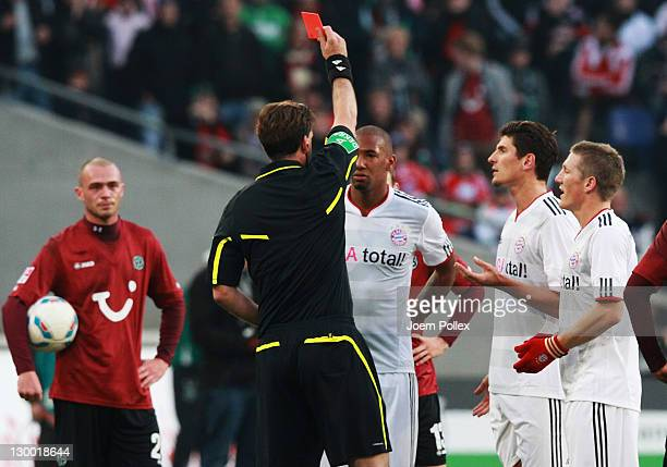 Jerome Boateng of Muenchen gets the red card from referee Manuel Graefe during the Bundesliga match between Hannover 96 and FC Bayern Muenchen at AWD...