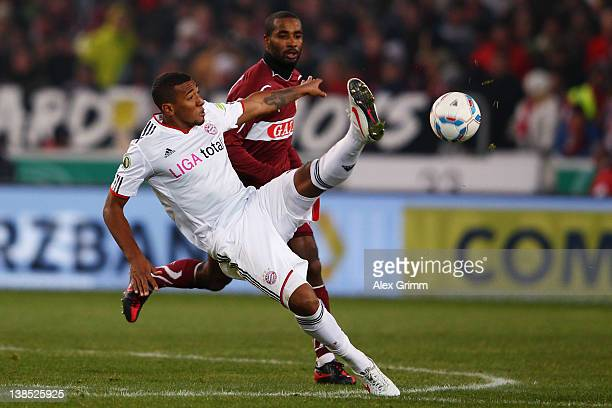 Jerome Boateng of Muenchen is challenged by Cacau of Stuttgart during the DFB Cup Quarter Final match between VfB Stuttgart and Bayern Muenchen at...