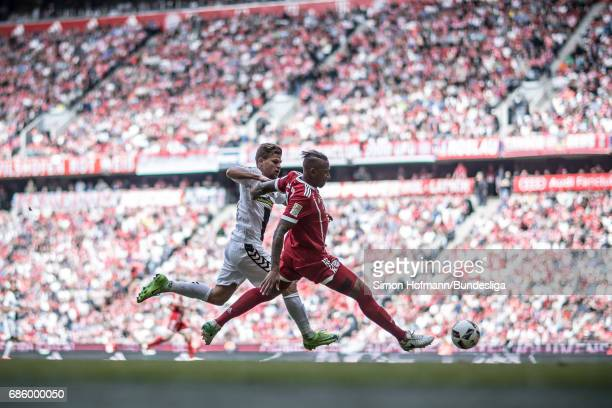 Jerome Boateng of Muenchen is challenged by Florian Niederlechner of Freiburg during the Bundesliga match between Bayern Muenchen and SC Freiburg at...