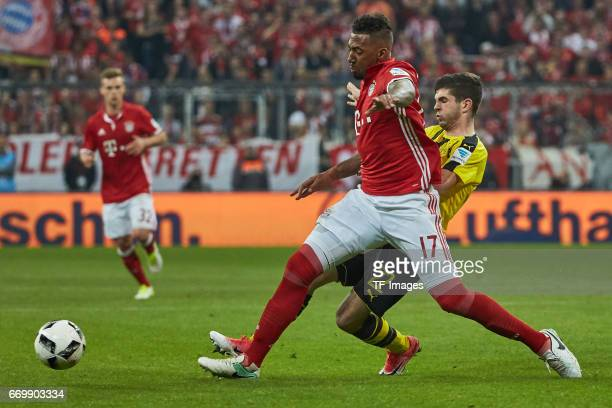 Jerome Boateng of Munich and Christian Pulisic of Dortmund battle for the ball during the Bundesliga match between Bayern Muenchen and Borussia...