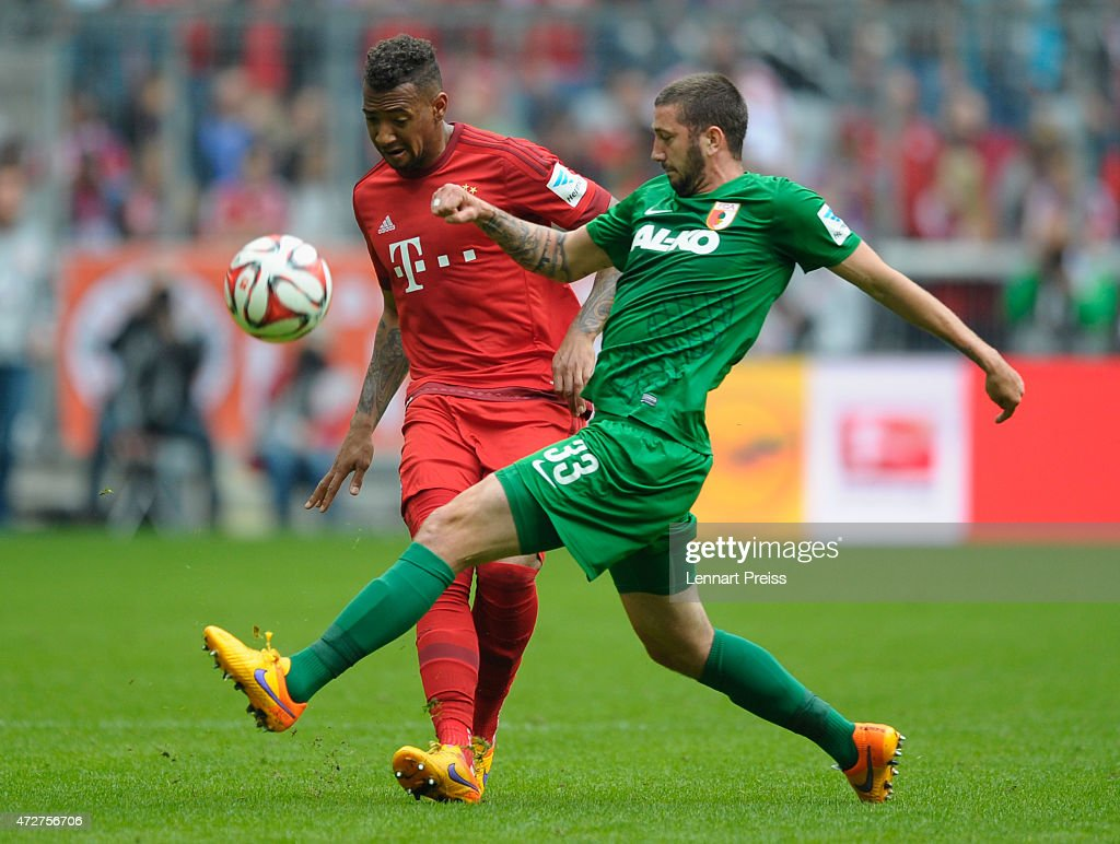 Jerome Boateng of Munich challenges Sascha Moelders of Augsburg during the Bundesliga match between FC Bayern Muenchen and FC Augsburg at Allianz...