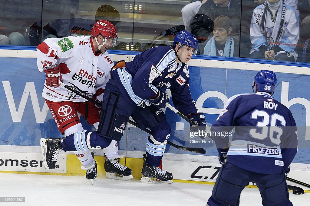 Jerome Flaake (R) of Hamburg battles for the puck with <a gi-track='captionPersonalityLinkClicked' href=/galleries/search?phrase=Mirko+Luedemann&family=editorial&specificpeople=712887 ng-click='$event.stopPropagation()'>Mirko Luedemann</a> (L) of Cologne during the DEL 1 Bundesliga match between Hamburg and Cologne at O2 World on December 7, 2012 in Hamburg, Germany.
