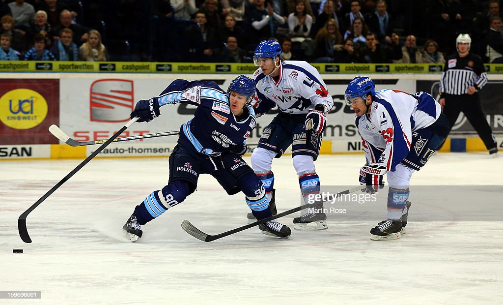 Jerome Flaake (L) of Hamburg battles for the puck with Steven Wagner (C) and Dominik Bittner (R) of Mannheim during the DEL match between Hamburg Freezers and Adler Mannheim at O2 World on January 18, 2013 in Hamburg, Germany.