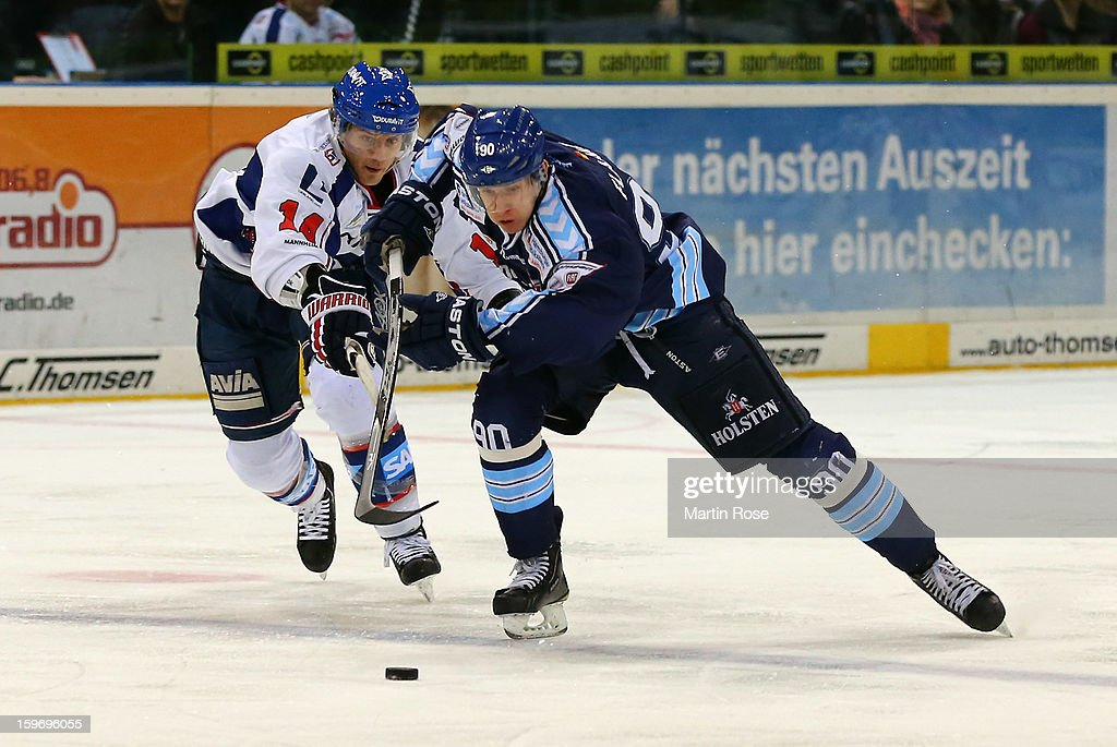 Jerome Flaake (R) of Hamburg battles for the puck with Steven Wagner (L) of Mannheim during the DEL match between Hamburg Freezers and Adler Mannheim at O2 World on January 18, 2013 in Hamburg, Germany.