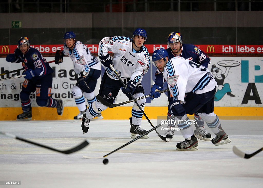 Jerome Flaake (L) of Hamburg Freezers watches Mathieu Roy (R) in action during the DEL ice hockey game between Red Bull Munich and Hamburg Freezers at Olympia Eishalle on December 28, 2012 in Munich, Germany.