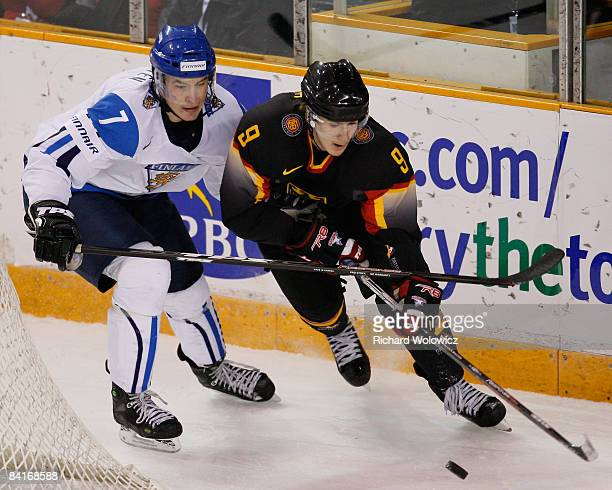 Jerome Flaake of Team Germany stick handles the puck while being defended against by Joonas Jarvinen of Team Finland during the relegation round of...