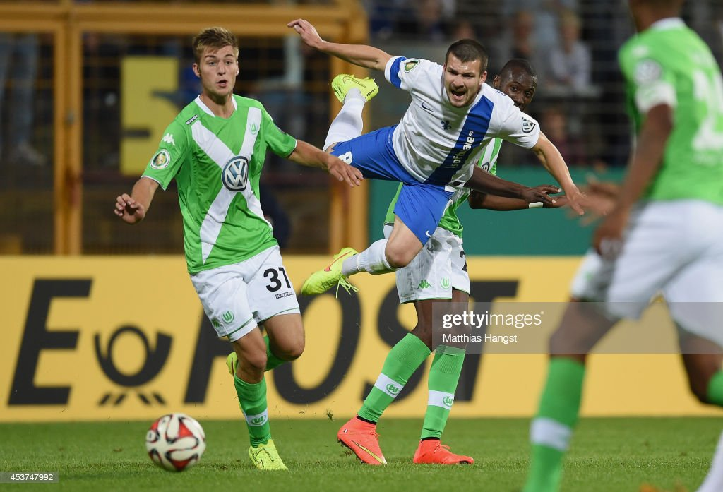Jerome Gondorf (C) of Darmstadt in action against Robin Knoche (L) of Wolfsburg and Josuha Guilavogui (R) of Wolfsburg during the DFB Cup first round match between SV Darmstadt 98 and VfL Wolfsburg at Stadion am Boellenfalltor on August 17, 2014 in Darmstadt, Germany.