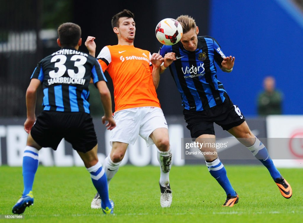 Jerome Gondorf of Darmstadt (C) is challenged by Artur Schneider of Saarbruecken (L) and Christian Eggert of Saarbruecken during the third Bundesliga match between 1. FC Saarbruecken and Darmstadt 98 on September 28, 2013 in Saarbruecken, Germany.