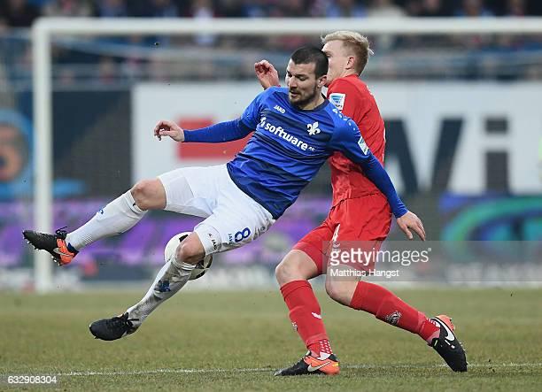 Jerome Gondorf of Darmstadt is challenged by Frederik Sorensen of Koeln during the Bundesliga match between SV Darmstadt 98 and 1 FC Koeln at Stadion...