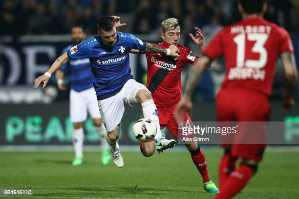 Jerome Gondorf of Darmstadt is challenged by Kevin Kampl of Leverkusen during the Bundesliga match between SV Darmstadt 98 and Bayer 04 Leverkusen at...
