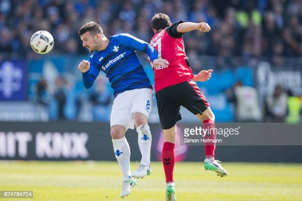 Jerome Gondorf of Darmstadt is challenged by Nicolas Hoefler of Freiburg during the Bundesliga match between SV Darmstadt 98 and SC Freiburg at...