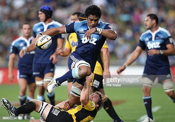 Jerome Kaino of the Blues is tackled by Jason Eaton of the Hurricanes during the round one Super 14 match between the Blues and the Hurricanes at...