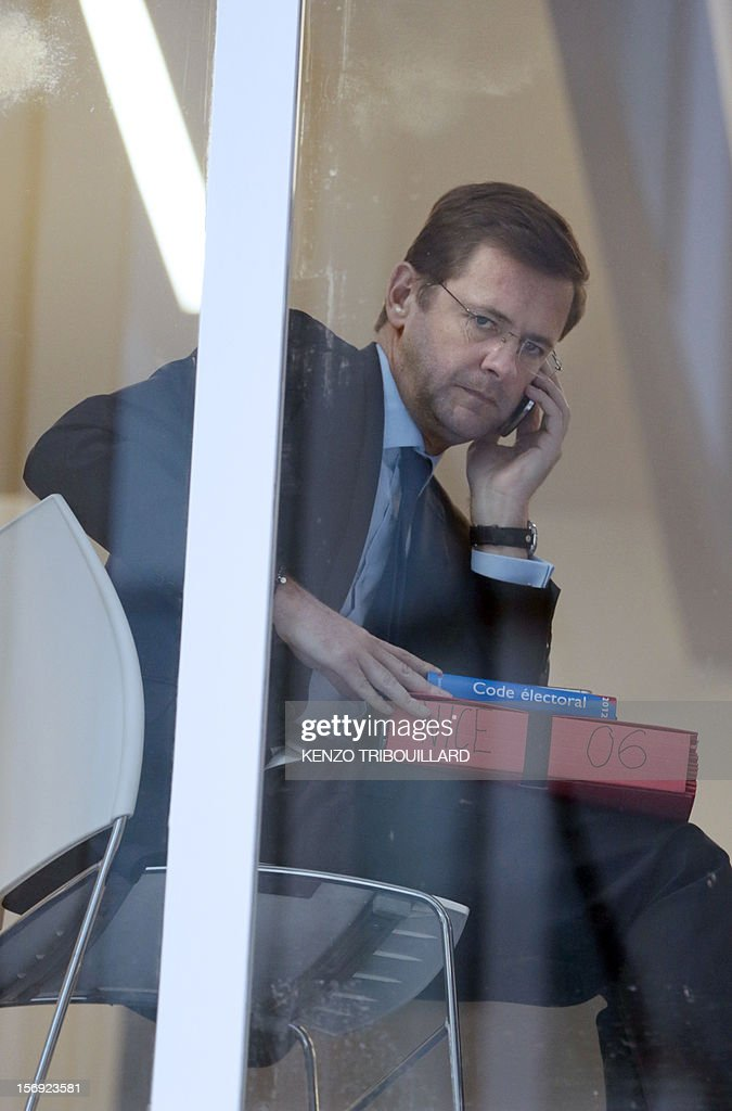 Jerome Lavrilleux (L), cabinet director of newly-elected president of the right-wing UMP opposition party, Jean-Francois Cope at the UMP's elections control committee (COCOE) talks on a mobile phone at the UMP party's headquarters in Paris on November 25, 2012. French lawyer and pro-Cope supporter, Francis Szpiner declared a 'desertion' the fact that French former Prime minister Francois Fillon's campaign director, Eric Ciotti slammed the door from the UMP's appeal elections control board, after considering it illegitimate and biased. Party heavyweight Juppe, a former premier and foreign minister, will hold a mediation meeting later in the day with the right-winger, who was declared the winner of November 22 knife-edge vote to pick a party leader, Jean-Francois Cope, and his centrist rival Francois Fillon. The talks are to establish who actually won the leadership and whether mutual allegations of ballot rigging have any foundation. AFP PHOTO KENZO TRIBOUILLARD
