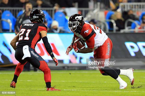 Jerome Messam of the Calgary Stampeders runs the ball toward Mitchell White of the Ottawa Redblacks during the first half of the 104th Grey Cup...