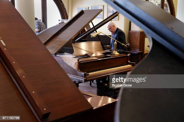 Jerome Murphy treasurer at M Steinert Sons looks over a Steinway Duoart one of over a dozen baby grand pianos to be sold at the M Steinert Sons...