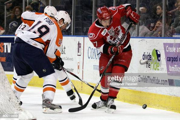 Jerome Samson of the Albany River Rats plays for possession of the puck against Scott Ford and Jason Pitton of the Bridgeport Sound Tigers during the...