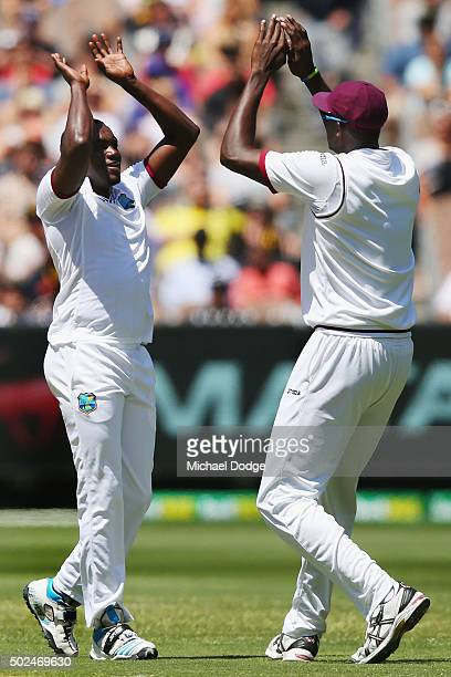 Jerome Taylor of the West Indies celebrates his wicket of David Warner of Australia with Jason Holder during day one of the Second Test match between...