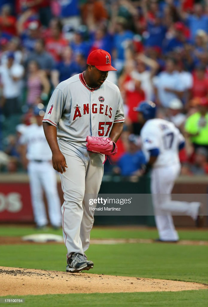 Jerome Williams #57 of the Los Angeles Angels steps off the mound after giving up a homerun against Nelson Cruz #17 of the Texas Rangers at Rangers Ballpark in Arlington on July 31, 2013 in Arlington, Texas.