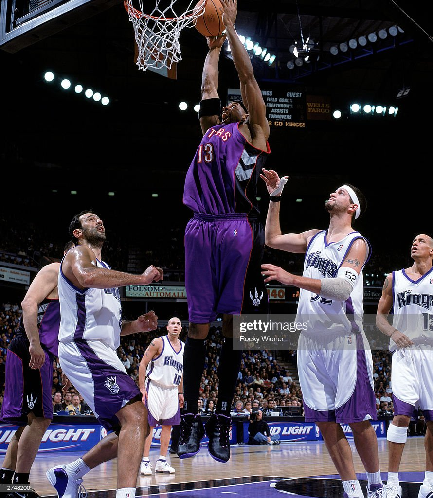 Jerome Williams #13 of the Toronto Raptors goes to the basket between Vlade Divac #21 and Brad Miller #52during the NBA game against the Sacramento Kings at Arco Arena on November 14, 2003 in Sacramento, California. The Kings won 94-64.