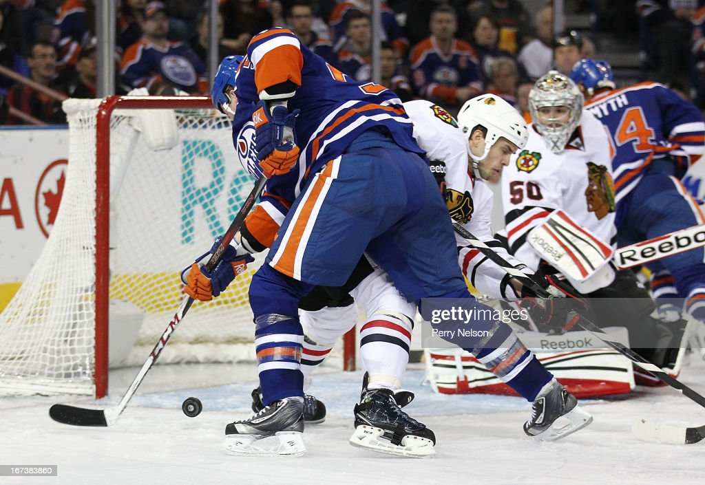 Jerred Smithson #52 of the Edmonton Oilers tries to knock a loose puck in the net against the Chicago Blackhawks at Rexall Place on April 24, 2013 in Edmonton, Canada.