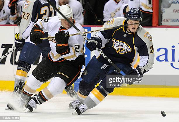 Jerred Smithson of the Nashville Predators lifts the stick of Todd Marchant of the Anaheim Ducks during an NHL game on March 24 2011 at Bridgestone...