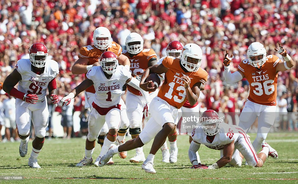 Jerrod Heard of the Texas Longhorns carries the ball against Charles Tapper of the Oklahoma Sooners Dominique Alexander of the Oklahoma Sooners and...