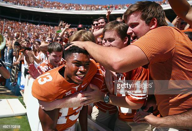 Jerrod Heard of the Texas Longhorns celebrates with fans after beating the Oklahoma Sooners 2417 during the ATT Red River Showdown at the Cotton Bowl...