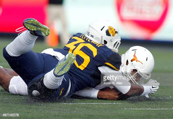 Jerrod Heard of the Texas Longhorns recovers a fumbled snap against Shaq Petteway of the West Virginia Mountaineers in the first half during the game...