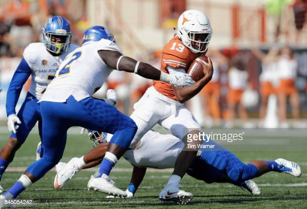 Jerrod Heard of the Texas Longhorns runs past Ethan Aguayo and Jamal Scott of the San Jose State Spartans in the third quarter at Darrell K...