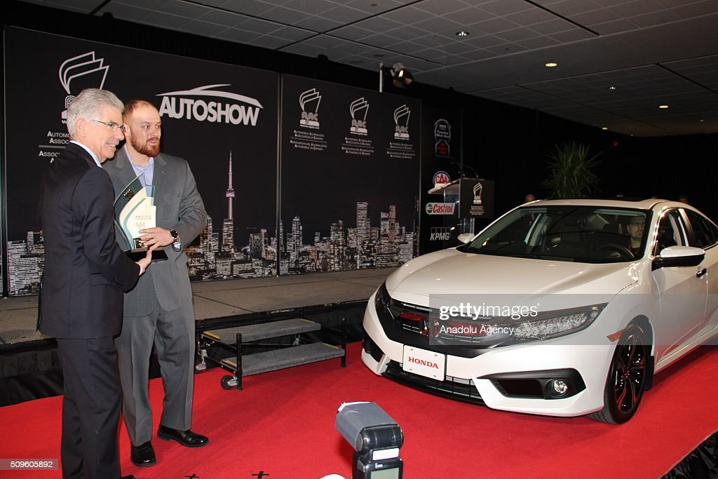 Jerry Chenkin (L), President and CEO of Honda Canada Inc. holds the award as the Honda Civic has been named the 2016 Canadian Car of the Year, during the Canada Auto Show at Toronto Metro Convention Center in Toronto, Canada on February 11, 2016.