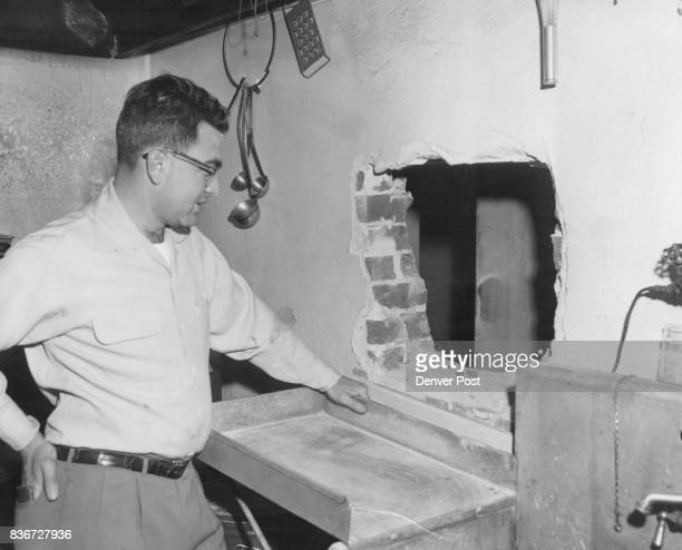 Jerry Feld owner of the Club fourOFour 404 Broadway looks at hole in brick wall made by burglars who got $9450 from a safe in the tavern $4950 of it...