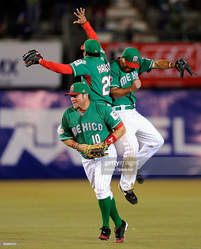 Jerry Hairston, Jr., #25 (C) of Mexico and Scott Hairston #14 (R) body slam as Karim Garcia #10 joins them after defeating South Africa, 14-3, to advance in the World Baseball Classic in the 2009 World Baseball Classic Pool B match on March 9, 2009 at the Estadio Foro Sol in Mexico City, Mexico.