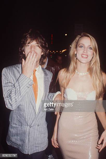 Jerry Hall and Mick Jagger walking together in to event Mick Jagger blows a kiss at camera circa 1980 New York