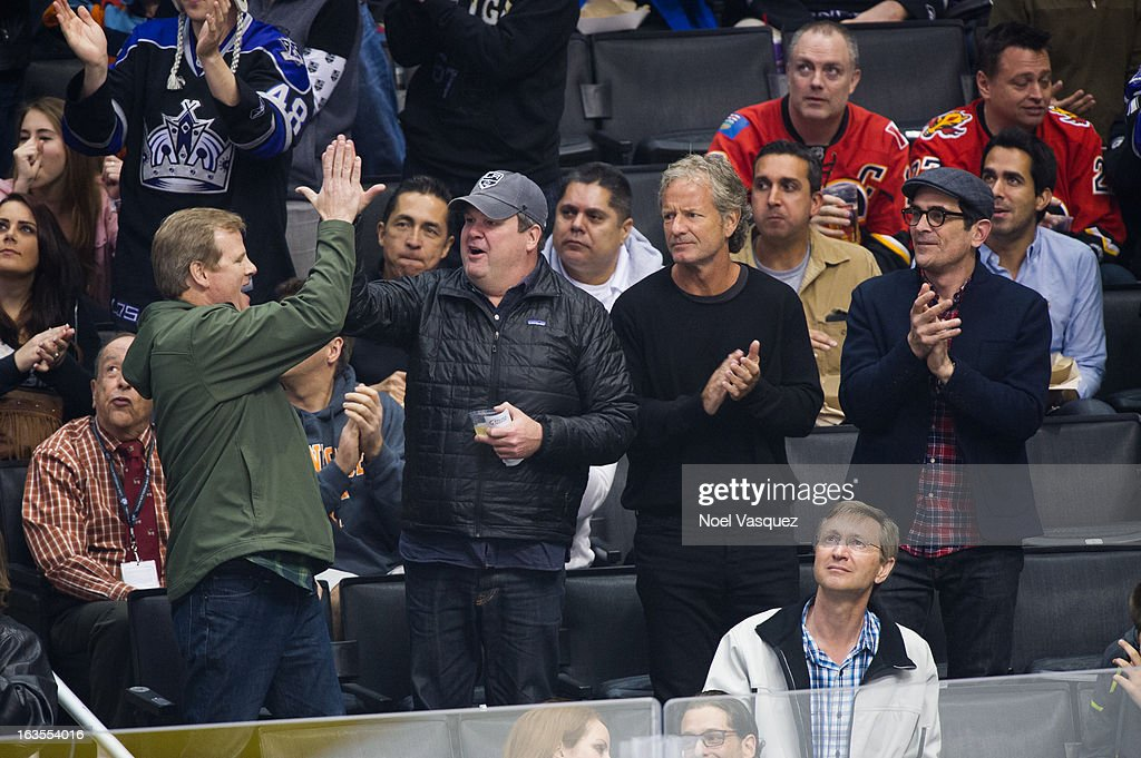 Jerry Lambert, Eric Stonestreet, guest and Ty Burrell attend a hockey game between the Calgary Flames and Los Angeles Kings at Staples Center on March 11, 2013 in Los Angeles, California.