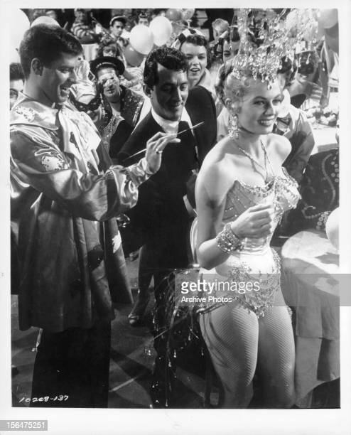 Jerry Lewis and Dean Martin painting on the back of Anita Ekberg in a scene from the film 'Artists And Models' 1955