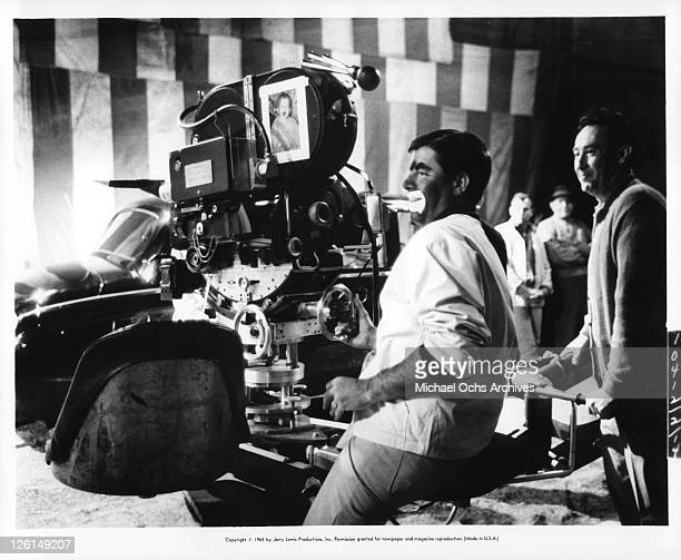 Jerry Lewis on stage with a clowns mouth operating a camera in a scene from the film 'The Family Jewels' 1965