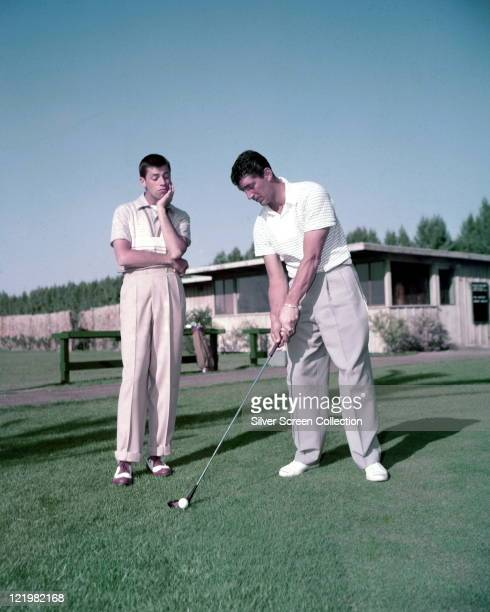 Jerry Lewis US actor and comedian watches as Dean Martin US actor and singer prepares to teeoff on a golf course USA circa 1952