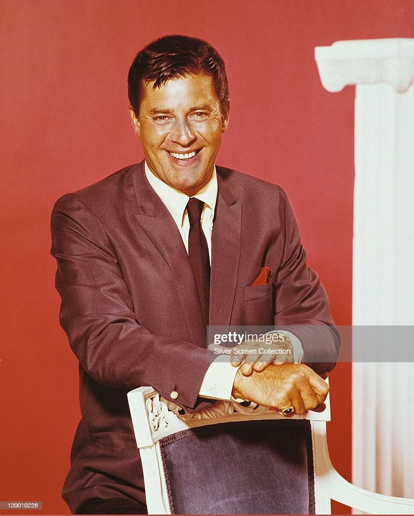 <a gi-track='captionPersonalityLinkClicked' href=/galleries/search?phrase=Jerry+Lewis+-+Comedian&family=editorial&specificpeople=202947 ng-click='$event.stopPropagation()'>Jerry Lewis</a>, US comedian and actor, wearing a grey jacket, white shirt and black tie and smiling in a studio portrait, against a red background, circa 1965.