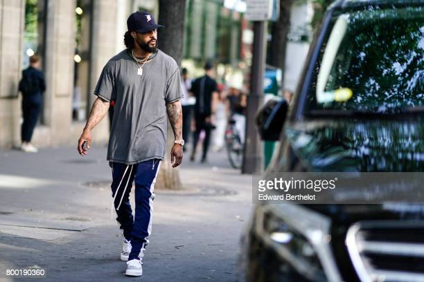 Jerry Lorenzo from Fear of God wears a blue cap a gray tshirt sportswear pants and sneakers after the CDG Comme des Garcons show during Paris Fashion...