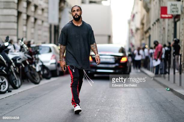 Jerry Lorenzo from Fear of God wears a gray tshirt sportwear pants and sneakers outside the OAMC show during Paris Fashion Week Menswear...