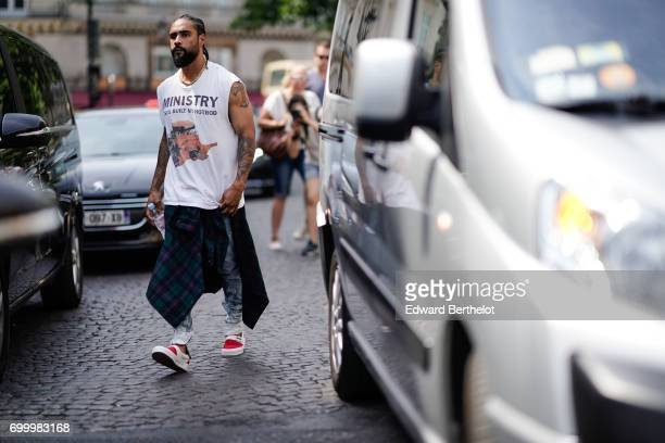 Jerry Lorenzo wears a white sleeveless top blue jeans red sneakers outside the Louis Vuitton show during Paris Fashion Week Menswear Spring/Summer...