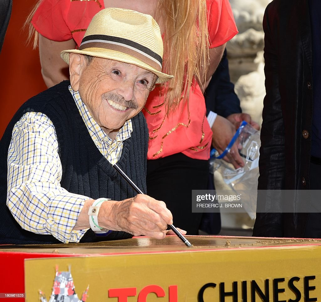 Jerry Maren, 93, one of two remaining 'Munchkins' from the 'Wizard of Oz' fame, signs his autograph in the cement on his way to becoming the oldest and smallest honoree in a hand and foot ceremony in the history of what was formerly known as Grauman's, or Mann's Chinese Theater, now renamed the TCL Chinese Theater IMAX in Hollywood, California on September 18, 2013. The theater will host the first ever IMAX 3D version of the Wizard of Oz in an exclusive one-week engagement beginning on September 20. AFP PHOTO/Frederic J. BROWN