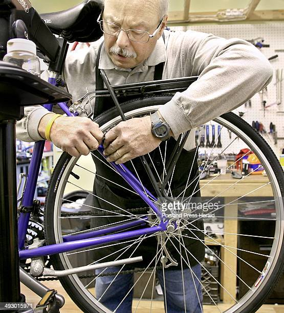 Jerry Morin of Jerry's Bike Barn sets the rear brakes properly to allow the brake pads to meet the rim at the same time during spring maintenance on...
