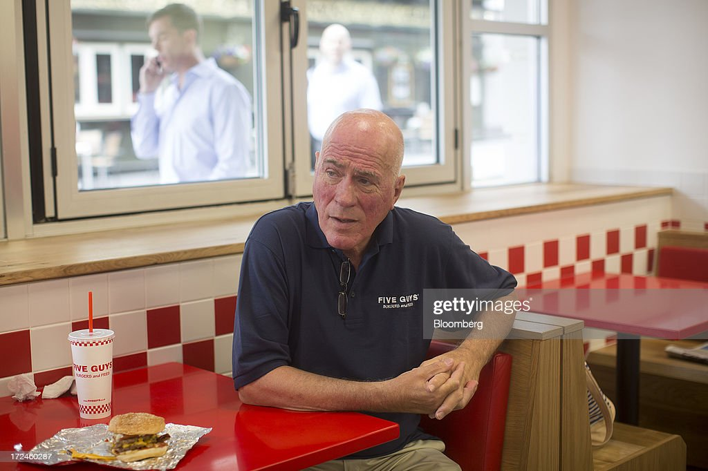 Jerry Murrell, founder of Five Guys, sits with a cheeseburger at a booth inside the company's new hamburger outlet in London, U.K., on Tuesday, July 2, 2013. Five Guys, the U.S. burger restaurant chain which is set to open its first U.K. store in Covent Garden on July 4, is a family outfit that started in Washington, D.C., in 1986, and has expanded to more than 1,000 locations in the U.S. and Canada. Photographer: Simon Dawson/Bloomberg via Getty Images