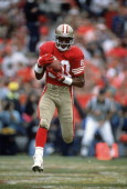 Jerry Rice of the San Francisco 49ers catches a pass during an NFL football game circa 1990 at Candlestick Park in San Francisco California Rice...