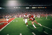 Jerry Rice of the San Francisco 49ers runs with the ball towards the end zone while pursued by Lewis Billups of the Cincinnati Bengals during Super...