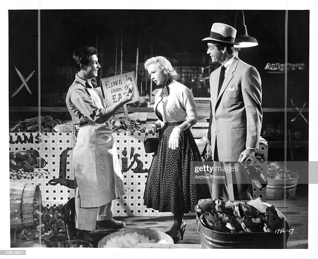 Jerry Riggio tries to sell food to Piper Laurie and Rory Calhoun in a scene from the film 'Ain't Misbehavin'' 1955