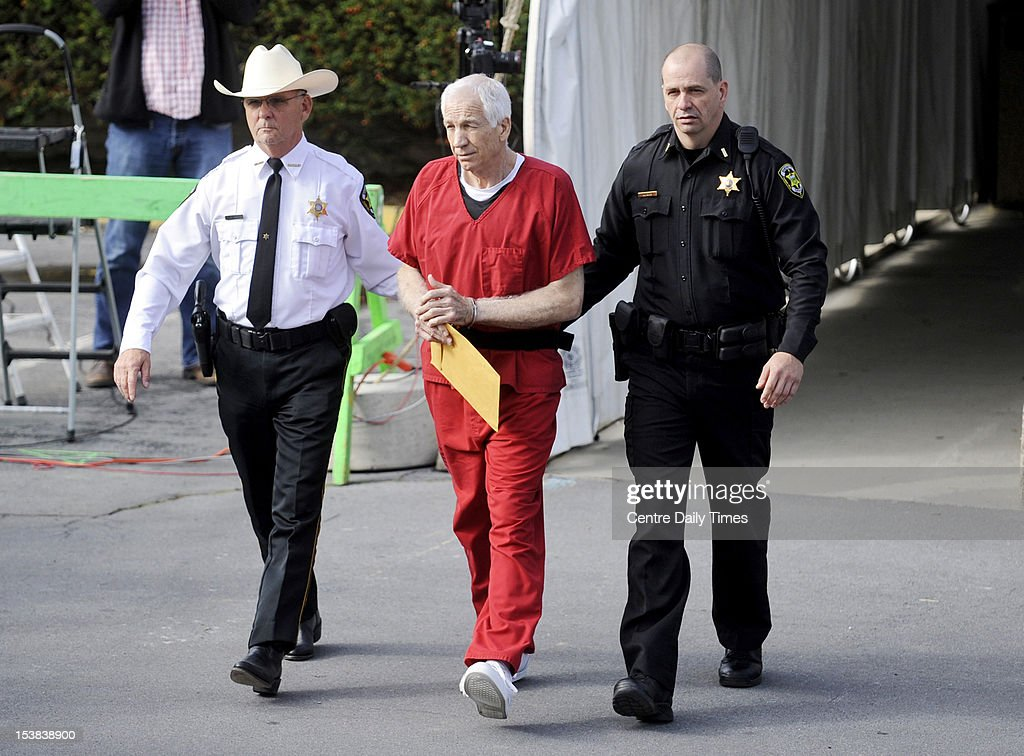 <a gi-track='captionPersonalityLinkClicked' href=/galleries/search?phrase=Jerry+Sandusky&family=editorial&specificpeople=8608969 ng-click='$event.stopPropagation()'>Jerry Sandusky</a>, center, leaves the courthouse in handcuffs after the judge ordered at least 30 years in prison at his sentencing, Tuesday, October 9, 2012, at the Bellefonte Courthouse in Bellefonte, Pennsylvania.