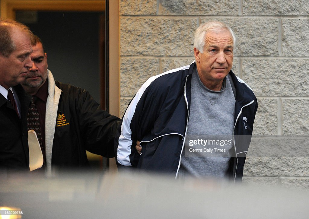 Jerry Sandusky, former Penn State assistant football coach, is escorted to a police car after being charged with additional counts of sexual abuse involving two more boys, Wednesday, December 7, 2011, in Bellefonte, Pennsylvania.