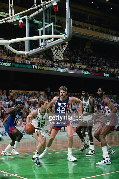 Jerry Sichting of the Boston Celtics moves the ball in the lane against Mike Gminski and Buck Williams of the New Jersey Nets during a game played in...